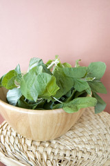 spinach in bowl with pink background