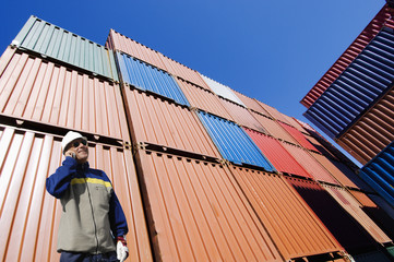 port worker with stacks of cargo containers, shipping