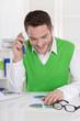 Positiv gestimmer Business Mann sitzend am Schreibtisch