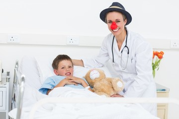 Doctor in clown costume with boy in hospital
