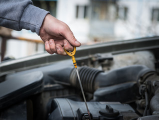 Auto Mechanic checking oil. Selective focus.