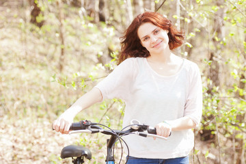 beautiful young woman with bicycle in spring forest