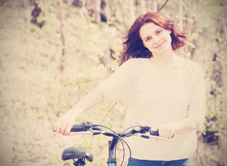 beautiful young woman with bicycle in spring forest, instagram r