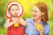 family mother and baby daughter drinking orange juice in the sum