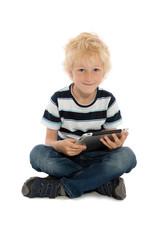 Junge sitzt mit Tablet Computer am Boden