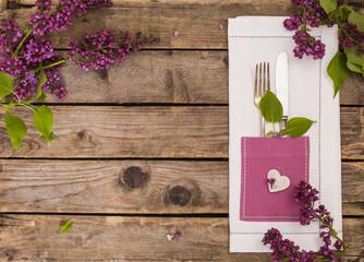 Tischset mit Besteck auf Holz mit Flieder