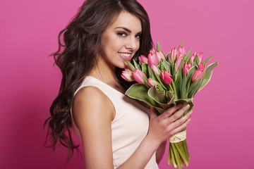 Lovely woman with bouquet of pink tulips