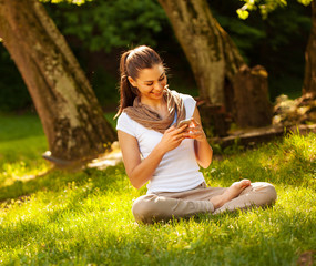 Attractive female typing sms message while sitting on grass.