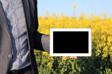 buisness man with a computer in a canola field