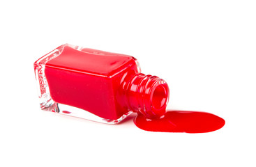 red polish bottle spilled over white background
