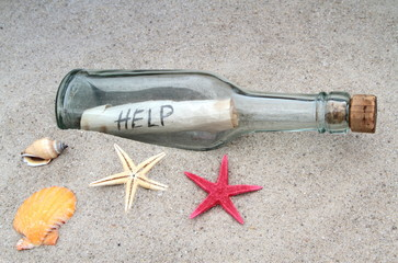 Message in a glass bottle on beach sand.