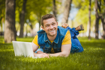 young man in the park lying on the grass with laptop