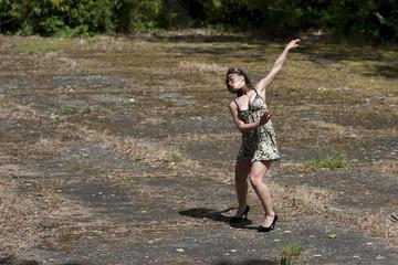 Danseuse en talons hauts sur un terrain vague.