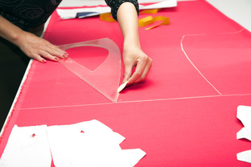 Tailor hands working with pink fabric