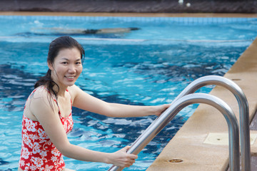 Portrait of Asian woman getting out of a swimming pool