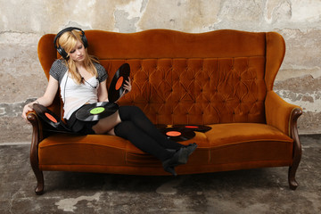 Blonde girl on sofa listening to music with headphones
