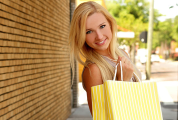 Pretty blonde young woman with shopping bag smiling