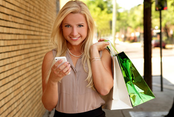 Pretty young woman with shopping bags and mobile phone smiling