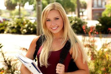 Pretty young blonde student with books and backpack