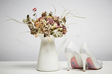 Bridal shoes and dried flowers in vase