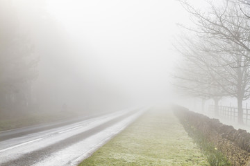 Road disappearing into fog