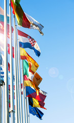 EU Member flags in front of European Parliament with lens flare