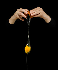 Egg Yolk dripping on black background.