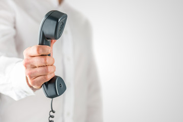 Man holding a landline telephone receiver