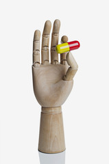 Large pill between an artist's manikin's fingers