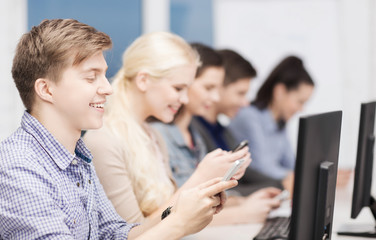 students with computer monitor and smartphones