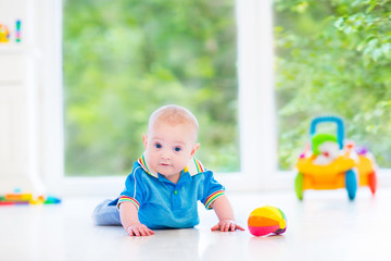 Funny baby boy playing with a colorful ball and toy car