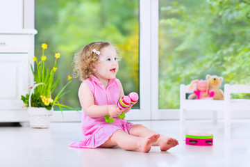 Cute curly toddler girl playing tambourine in a sunny white room