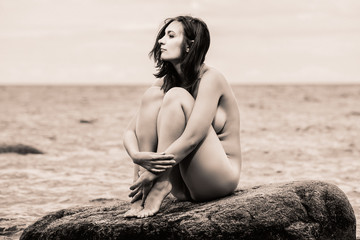 nude woman sitting on stone