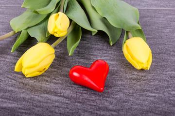 gelbe Tulpen mit rotem Herz auf Stein