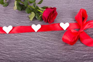 rote Rose mit herzgeschmückter Schleife