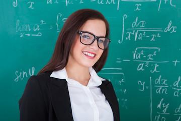 Happy Teacher Against Chalkboard