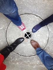 piedi disposti a croce su tombino