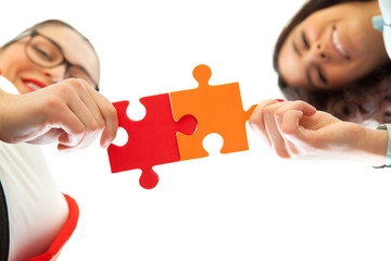 business women assembling jigsaw puzzle and