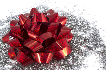 Red gift bow on white background with silver glitter