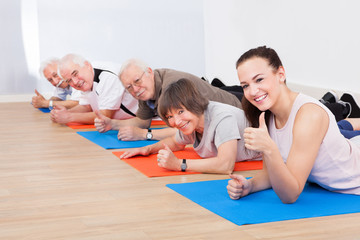 Trainer And Senior Customers At Gym