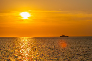 sunset on sea with ferry in distance