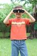 Little boy with binocular exploring in a garden