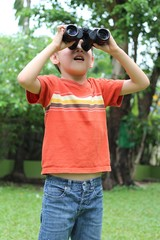Little boy with binocular exploring in a garden