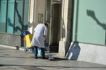 mujer de la limpieza fregando un portal