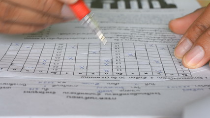 Teacher checking of students exam in scantron sheet