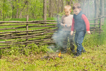 Proud little boys standing watching a burning fire