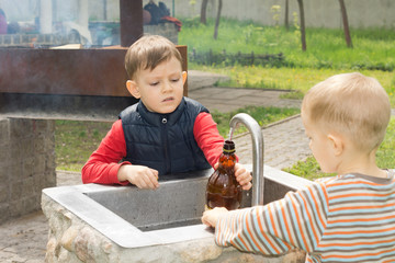 Two young boys filling a bottle of water