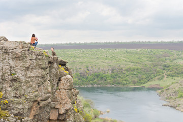 Young couple sitting on a steep rocky cliff