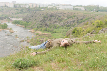 Man enjoying the sun lying outstretched on a hill