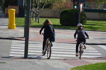 madre e hija en bicicleta en la ciudad